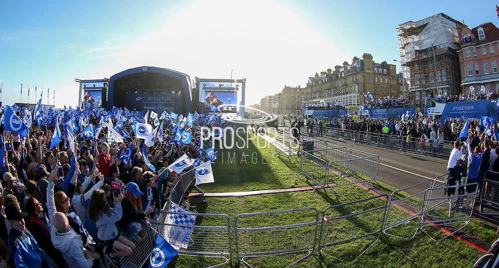 Brighton fans with flags see the players open top buses arrive at the stage during the Brighton & Hove Albion Football Club Promotion Parade at Brighton Seafront, Brighton, United Kingdom on 14 May 2017. Photo by Phil Duncan.