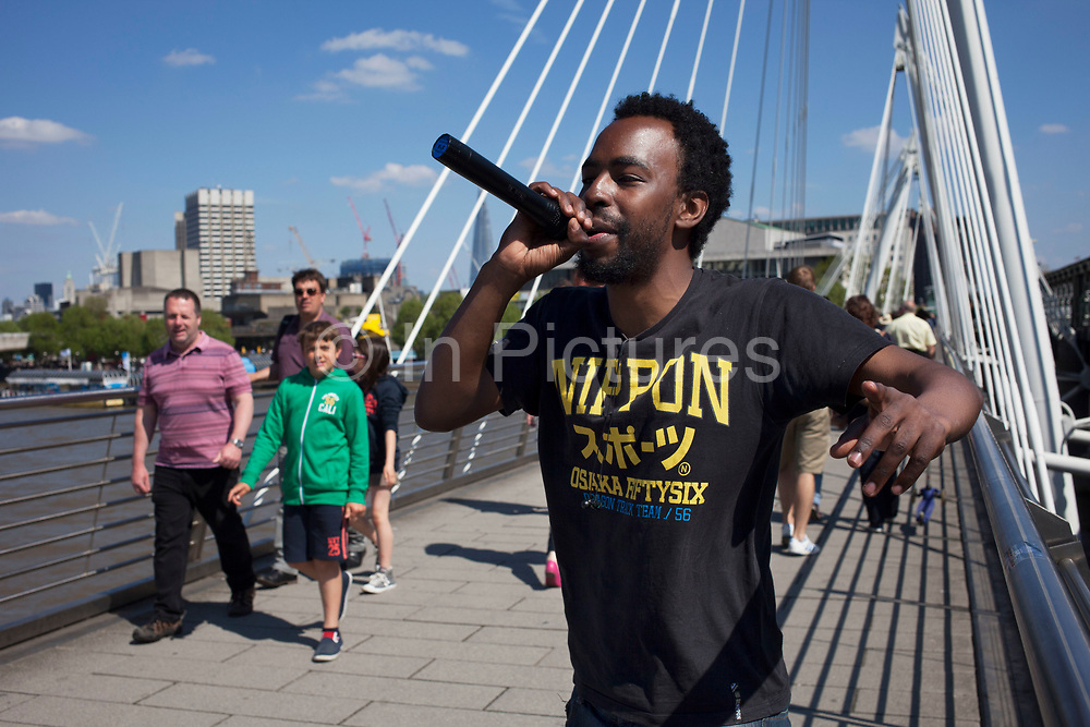 Busker rapping on Golden Jubilee Bridge perform music to passers by. This is a popular place for busking as there is a constant and reliable footfall of people. London, UK.