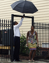 US President Barack Obama lifts his umbrella over a gate for First Lady Michelle Obama as they tour the the Columbia Parc Apartment Development in New Orleans, LA, USA, on August 29, 2010. President Obama was at the University to give a speech marking the fifth anniversary of Hurricane Katrina. Photo by A.J. Sisco/UPI/ABACAPRESS.COM  | 242236_002 New Orleans