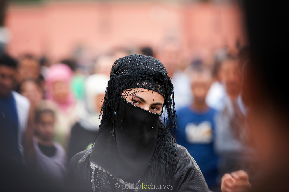 A street performer, a man dressed as a woman, entertaining crowds in the Djemaa el Fna in the medina of Marrakech, Morocco