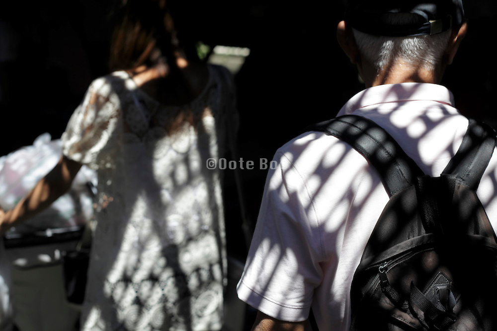 people walking with grating shadow projection overlay