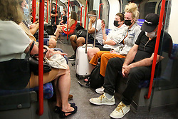 © Licensed to London News Pictures. 13/06/2021. London, UK. Commuters wearing face coverings travelling on the underground. Prime Minister Boris Johnson may delay the final lifting of coronavirus lockdown restrictions in England amid a rise in Covid-19 cases of the Delta variant. A final decision is expected to be taken today ahead of a formal announcement by the Prime Minister at a news conference on Monday. Photo credit: Dinendra Haria/LNP