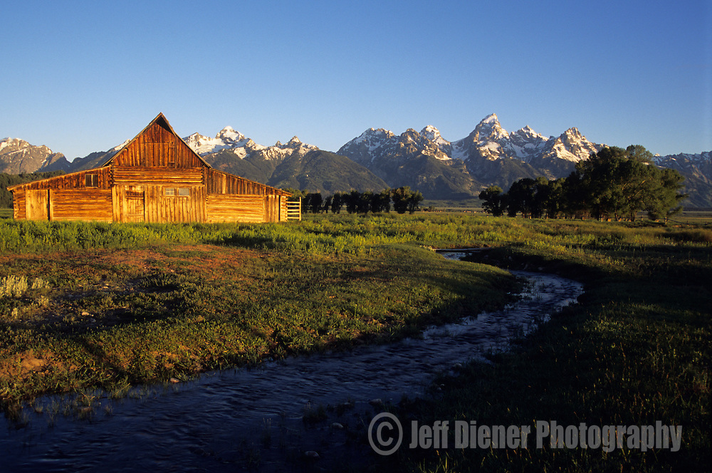 Sunrise lights a historic barn in front of the Tetons in Grand Teton National Park, Jackson Hole, Wyoming.