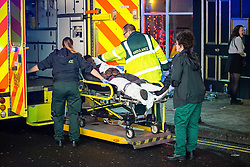 © Licensed to London News Pictures . 27/12/2015 . Wigan , UK . Paramedics tend to a man who has collapsed in the street . Revellers in Wigan enjoy Boxing Day drinks and clubbing in Wigan Wallgate . In recent years a tradition has been established in which put on fancy dress for a Boxing Day night out . Photo credit : Joel Goodman/LNP