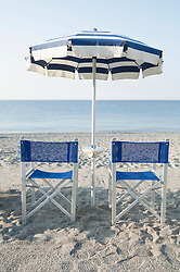 Two beach chairs umbrella ocean summer empty