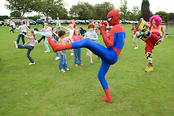 Spiderman and a clown leading a Superhero workout for children at a Parklife summer activities event,