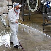 Nederland Giessen 26 augustus 2009 20090826 ..Serie over levensmiddelensector                                                                                      .HAK fabriek, verwerking zilveruitjes. Werknemer spuit de werkvloer schoon. .Worker cleaning the floor ..Foto: David Rozing
