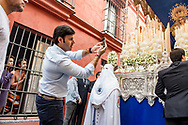 A young couple of tourists is woken up, early morning on Easter day, by the passage of a float carrying the Virgin Mary in a narrow alley in the centre of Seville. Spain