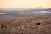 Visitors watching sunset over horizon on desert, Valle de la Luna in Atacama Desert, Chile