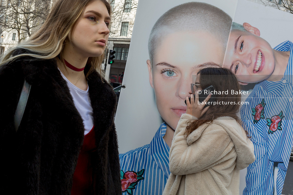 "Models stand next to a street billboard for high-street retailer New Look, outisde London Fashion Week in the Strand, on 17th Febriary 2017, in London, England, United Kingdom. London Fashion Week is a clothing trade show held in London twice each year, in February and September. It is one of the ""Big Four"" fashion weeks, along with the New York, Milan and Paris. The fashion sector plays a significant role in the UK economy with London Fashion Week alone estimated to rake in £269 million each season. The six-day industry event allows designers to show their collections to buyers, journalists and celebrities and also maintains the city's status as a top fashion capital. (Photo by Richard Baker / In Pictures via Getty Images)"