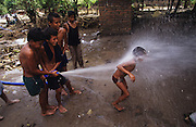 Central America, Honduras, Tegucigalpa, Choluteca. Devastation in the aftermath of Hurricane Mitch. High winds and flooding. Refugees. Boys playing with hosepipe and spraying water. Infrastructure destroyed.