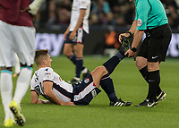 Football - 2017 / 2018 EFL (League) Cup - Third Round: West Ham United vs. Bolton Wanderers<br /> <br /> In a game offering little second half action the referee Simon Hooper turns physio and helps Jeff King (Bolton Wanderers) with his cramp injury at the London Stadium.<br /> <br /> <br /> COLORSPORT/DANIEL BEARHAM