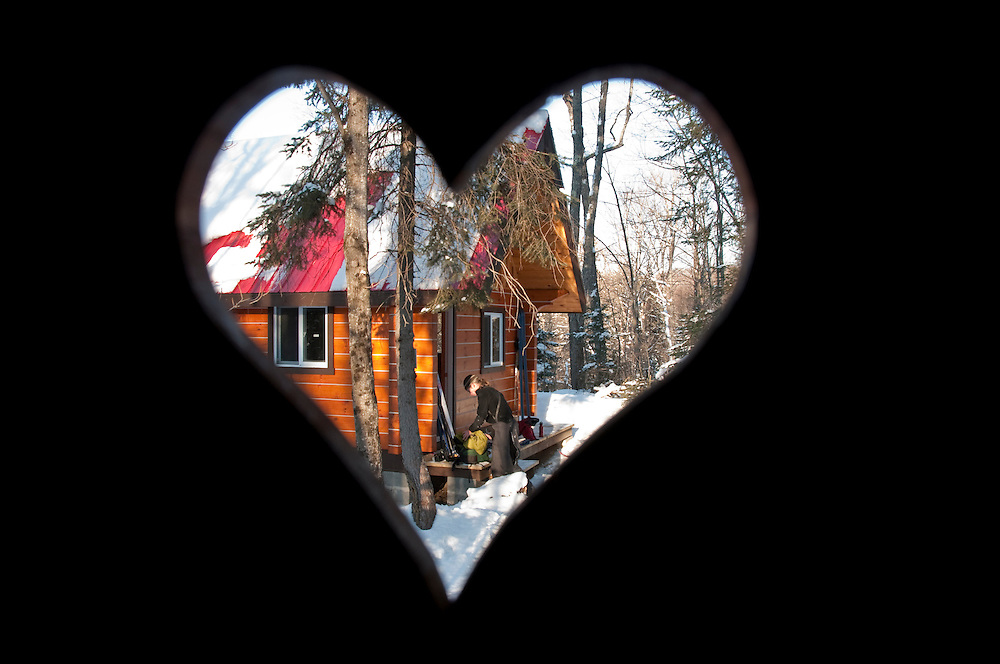 A backwoods cabin at Stokely Creek Lodge is seen through the heart window in an outhouse.
