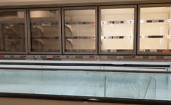 © Licensed to London News Pictures. 23/07/2021. London, UK. Empty freezer shelves in a Sainsbury's store in London. The government has announced that daily contact testing will be rolled out to workplaces in the food sector, so staff who have been pinged by the COVID-19 app can keep working if they test negative rather than isolating. This is because a number of supermarkets are reporting empty shelves as they, wholesalers and hauliers are struggling to ensure enough food and fuel supplies, after the COVID-19 NHS app alerted workers to isolate after being in contact with someone with COVID-19. Photo credit: Dinendra Haria/LNP