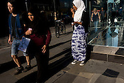 Young Mulsim girls walk through a London street, one carrying a shopping bag from the Guess shop with image of naked female.
