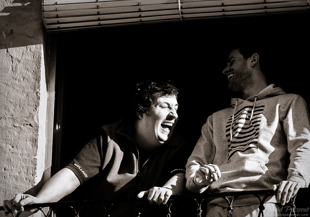 Two men laughing on a balcony.