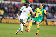 Bafetimbi Gomis of Swansea city (l) is challenged by Ryan Bennett of Norwich city.Barclays Premier league match, Swansea city v Norwich city at the Liberty Stadium in Swansea, South Wales  on Saturday 5th March 2016.<br /> pic by  Andrew Orchard, Andrew Orchard sports photography.