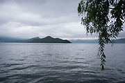 A cloudy day when the water is calm at Lugu Lake, Yunnan, China. Lugu Lake is located in the North West Yunnan plateau in the centre of Ninglang Yi Autonomous County in the Peoples Republic of China.