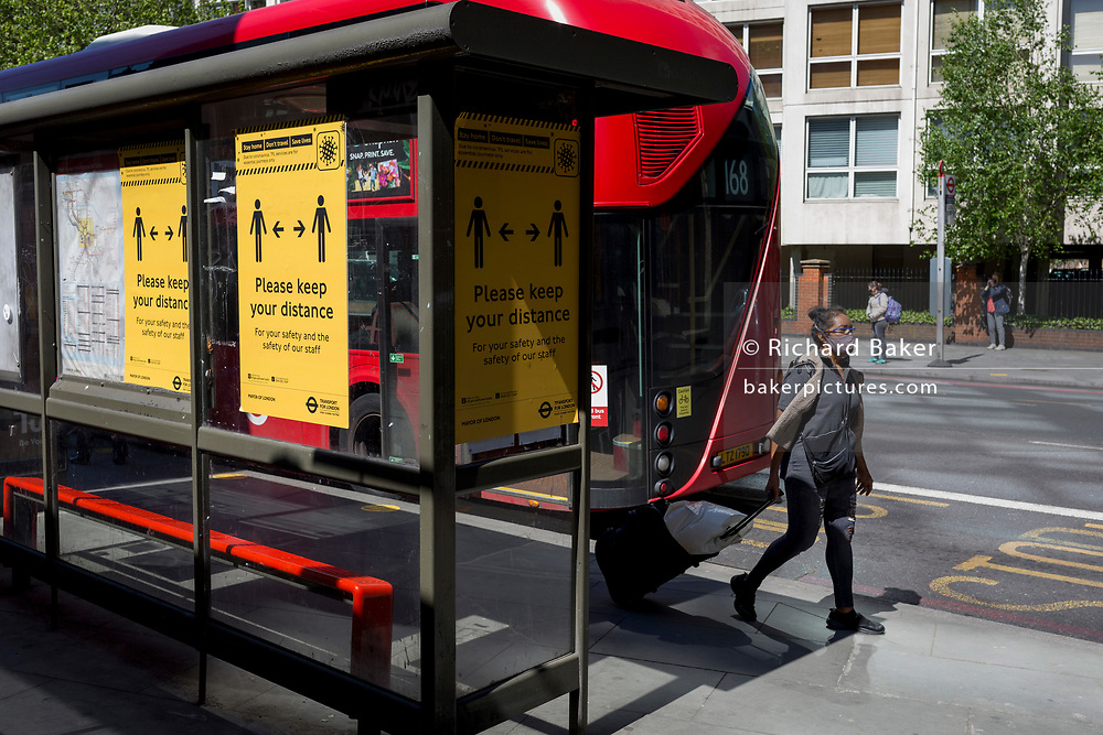 In the UK, 32,313 people have now died after testing positive for coronavirus which is now the highest death toll in Europe, even exceeding that of Italy. With UK lockdown continuing, a passenger pulls a suitcase while social distancing measures are posted at bus stops around the capital in preparation of a return to work and public transport for some workers in the near future, on 5th May 2020, in London, England.