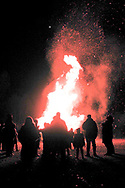 People standing around a large bonfire at night