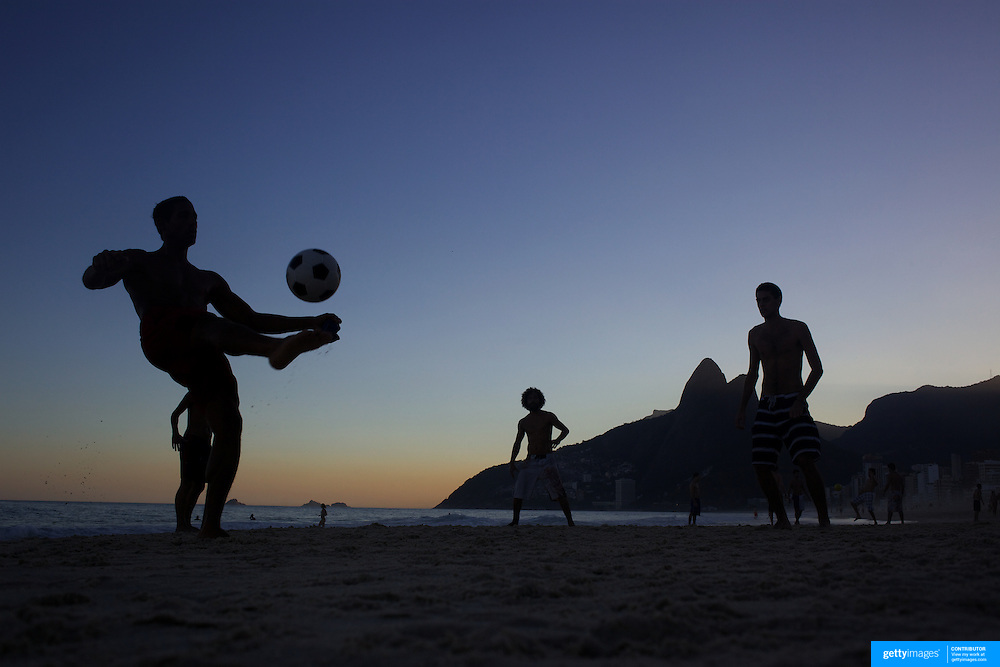 Locals play football during the late afternoon sunset on Ipanema beach, Rio de Janeiro,  Brazil. 6th July 2010. Photo Tim Clayton..The beaches of Rio de Janeiro, provide the ultimate playground for locals and tourists alike. Beach activity is in abundance as beach volley ball, football and a hybrid of the two, foot volley, are played day and night along the length and breadth of Rio's beaches. .Volleyball nets and football posts stretch along the cities coastline and are a hive of activity particularly at it's most famous beaches Copacabana and Ipanema. .The warm waters of the Atlantic Ocean provide the ideal conditions for a variety of water sports. Walkways along the edge of the beaches along with exercise stations and cycleways encourage sporting activity, even an outdoor gym is available at the Parque Do Arpoador overlooking the ocean. .On Sunday's the main roads along the beaches of Copacabana, Leblon and Ipanema are closed to traffic bringing out thousands of people of all ages to walk, run, jog, ride, skateboard and cycle more than 10 km of beachside roadway. .This sports mad city is about to become a worldwide sporting focus as they play host to the world's biggest sporting events with Brazil hosting the next Fifa World Cup in 2014 and Rio de Janeiro hosting the Olympic Games in 2016..