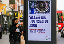 © Licensed to London News Pictures. 19/10/2020. London, UK. A shopper in north London walks past the government's publicity campaign 'TIME IS RUNNING OUT' for firms that trade with Europe to prepare for a no-deal Brexit. HMRC will contact over 200,000 firms that trade with the EU to set out the new customs and tax rules and how to deal with them. Photo credit: Dinendra Haria/LNP