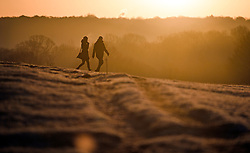 © Licensed to London News Pictures. 19/01/2020. London, UK. A couple walking at sunrise in a frost covered landscape at sunrise in Richmond Park in west London on a bright and freezing Winter morning. Photo credit: Ben Cawthra/LNP