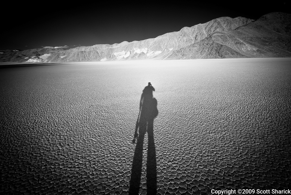 The shadow of the photographer stretches across the flat, cracked clay of this play at the Racetrack in Death Valley National Park.