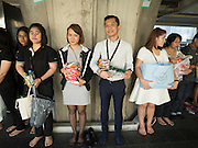 """29 NOVEMBER 2016 - BANGKOK, THAILAND:  People wait to donate alms to Buddhist monks at a special """"tak bat"""" or merit making ceremony in the Ratchaprasong skywalk of the Bangkok BTS system. The tak bat was to honor Bhumibol Adulyadej, the Late King of Thailand. Food and other goods were given to the monks, who in turn gave the items to charities that will distribute them to Bangkok's poor. More than 100 Buddhist monks participated in the merit making ceremony. The ceremony was organized by the merchants in the Ratchaprasong Intersection, which includes some of Bangkok's most upscale shopping centers.     PHOTO BY JACK KURTZ"""