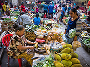 11 OCTOBER 2016 - UBUD, BALI, INDONESIA:  A woman buys fruit from a vendor in the morning market in Ubud. The morning market in Ubud is for produce and meat and serves local people from about 4:30 AM until about 7:30 AM. As the morning progresses the local vendors pack up and leave and vendors selling tourist curios move in. By about 8:30 AM the market is mostly a tourist market selling curios to tourists. Ubud is Bali's art and cultural center.     PHOTO BY JACK KURTZ