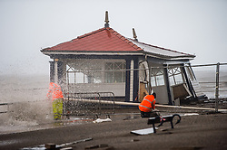 © Licensed to London News Pictures. 06/01/2014. Aberystwyth, UK. The iconic 1920's public shelter on Aberystwyth promenade, a listed building, slips into the sea after its foundations were gouged out by days of incessant stormy seas. At high tide at 11.20am on Monday 06 Jan 2014, a deep depression drives a huge ground swell of waves to crash into the promenade at Aberystwyth, already partly destroyed by the storms of the past three days..  Photo credit : Keith Morris/LNP