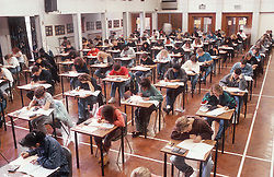 Secondary school pupils sitting at desks in school hall taking exam,