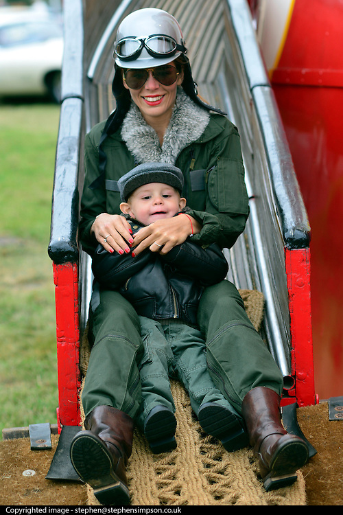 © Licensed to London News Pictures. 16/09/2012. Goodwood, UK .Elise Maillet and her son Charles aged 2 ride the helter skelter.  People enjoy the atmosphere at the 2012 Goodwood Revival. The event recreates the glorious days of motor racing and participants are encouraged to dress in period dress. Photo credit : Stephen Simpson/LNP