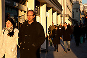 Couples out shopping on The Strand, London. As the evening sun casts long shadows it warms the faces of shoppers.