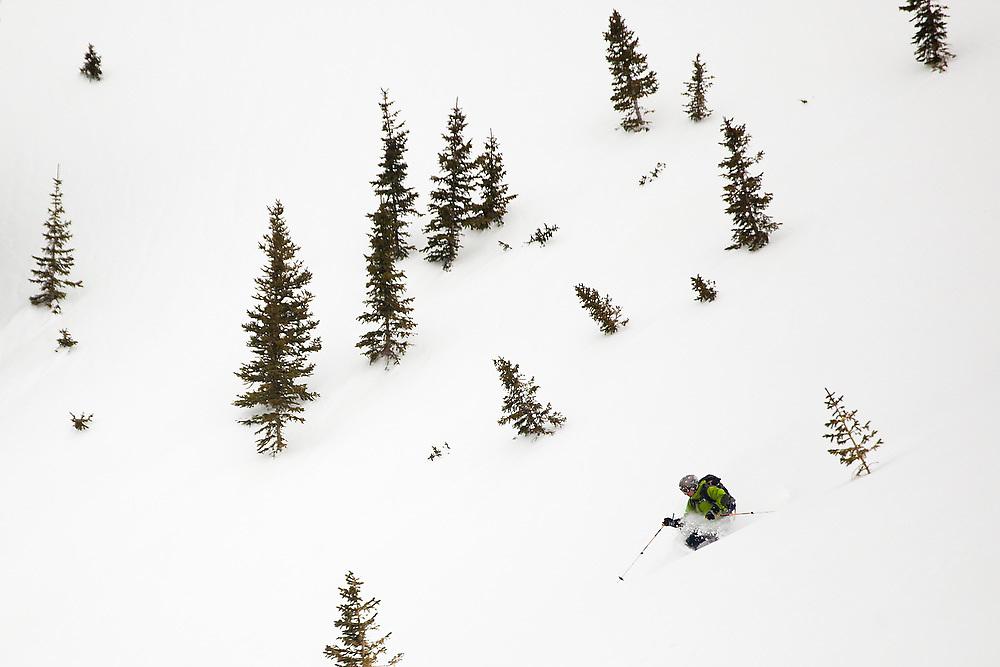 Backcountry skier Judd MacRae turns through deep powder in the open slopes below Hayden Peak, San Juan Mountains, Colorado.