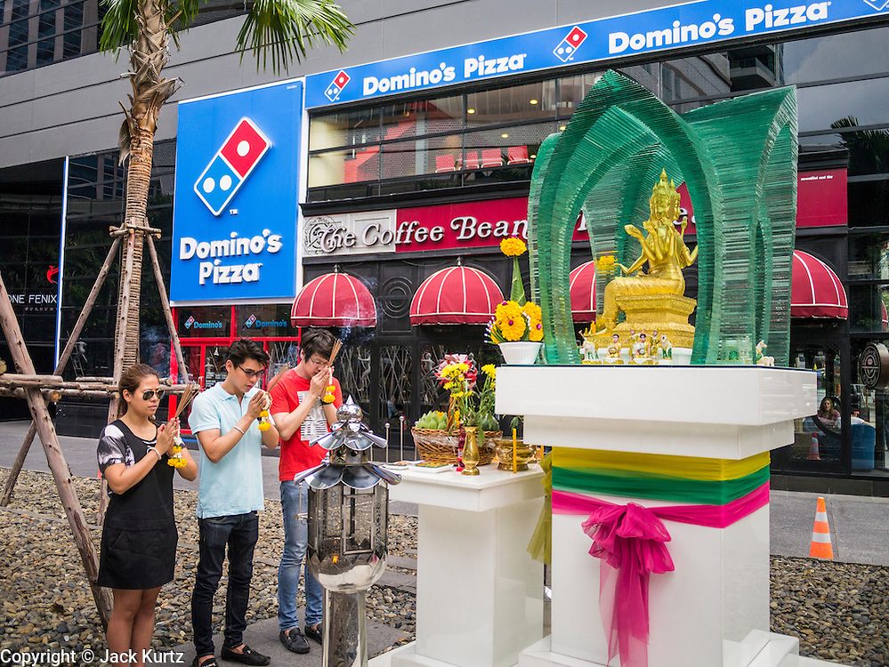11 JUNE 2013 - BANGKOK, THAILAND: Thais stop to pray at a spirit house in front of a Holiday Inn hotel with a Domino's Pizza and Coffee Bean and Tea Leaf in it. Spirit houses are a part of traditional Thai culture and religion.      PHOTO BY JACK KURTZ