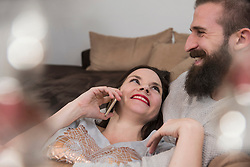 Woman talking on cell phone with her husband on sofa