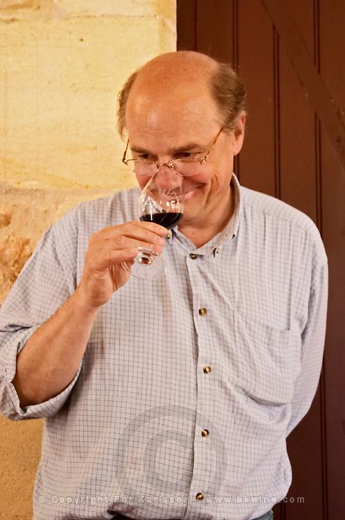 Jean-Francois Quenin, owner and wine maker, in the tasting room tasting a glass of his wine  Chateau de Pressac St Etienne de Lisse  Saint Emilion  Bordeaux Gironde Aquitaine France