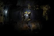 Valentina Zurro sulla macchina che taglia il carbone, sulle pareti i bulloni lunghi vari metri che fissano la roccia. Le reti bianche servono a impedire la caduta di piccoli frammenti