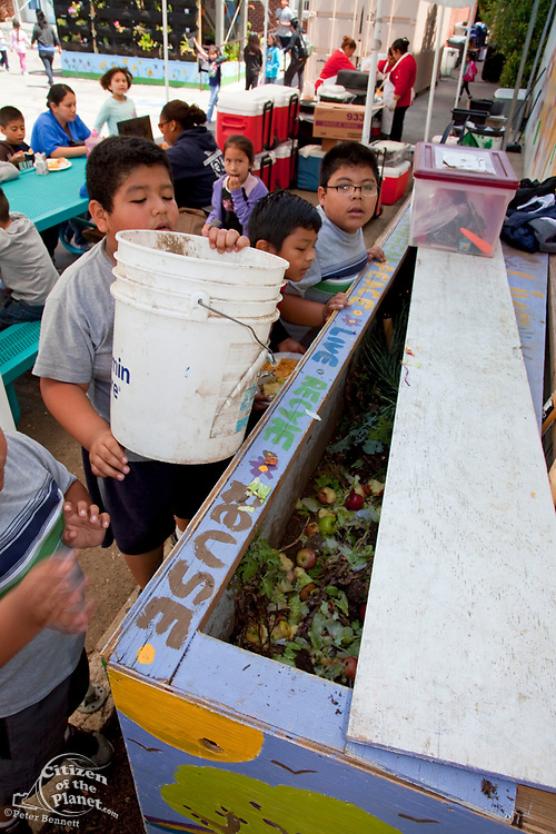 Young boys collect food for the worm compost bin after their class mates eat their lunch at the Downtown Value School, a charter school in downtown Los Angeles. The school uses gardens to teach students about gardening and also has a vertical garden, a flower and produce garden that goes around the school grounds and a small greenhouse. Los Angeles, California, USA