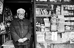 Shopkeeper standing in front of his small shop in a Beijing hutong