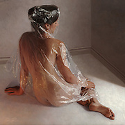 She IS an oil painting: Artist's amazingly detailed works of 'hyper-realistic' paintings that look like photographs<br /> <br /> At first glance, you think you are seeing a photo.<br /> But peer closer and maybe - just maybe - you can see the paint-strokes that belie the fact that these are actually hyper-realistic paintings.<br /> Each exquisitely detailed piece of work shows naked subjects wrapped in plastic foil - meaning Australian artist Robin Eley must pay close detail to each fold, each reflection, and the changing tones between plastic and flesh.<br /> It takes many many hours for Eley to produce a portrait, with his largest works taking five weeks apiece - working 90 hours per week.<br /> <br /> Born in London in 1978, but raised in Australia from the age of three, the artist has been exhibited in London and New York, among others, and he has been both a runner-up and highly-recommended in the Australian Doug Moran National Portrait Prize.<br /> Moving from commercial illustrations to portrait work a few years ago, one of his key themes is isolation, and he recently said: 'I was really thinking, getting down to the heart of what it was I wanted to say before recreating and re-imagining things that made me feel something.'<br /> <br /> Robin added: 'One of those things was the way we are experiencing isolation in the modern world.<br /> 'I'm the son of a parents who met in an overseas country neither was from.<br /> 'Mum was from China and had moved to London, isolated from her friends and family. Dad was from Adelaide. Today the isolation is different from theirs.<br /> 'We are so connected we don't even need to connect. Modern isolation is the technology we have actively embraced. <br /> 'We are all on Facebook where we don't have to ask our friends how they're going because we can see what they're doing.'<br /> Cellophane is his medium for this - it is something you can see through but not feel through.<br /> He said: 'It is a seductive existence where quantity trumps quality, where a smile is supplanted by a like button, and the accumulatio