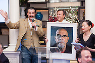 """Chef Daniel Boulud holds a self-portrait of Chuck Close as it is auctioned by Nicholas Lowry of Swann Auction Galleries at """"Burgundy, Black Truffles, and Denim,"""" a charity dinner at Restaurant DANIEL to benefit Citymeals-on-Wheels."""