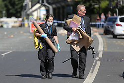 © Licensed to London News Pictures. 29/08/2016. Leeds, UK. Police carry evidence at what is believed to be the scene of shooting that took place last night. This is as yet unconfirmed by the police. The incident happened in the Chappeltown area of Leeds where the West Indian Carnival is taking place this weekend. Photo credit : Ian Hinchliffe/LNP