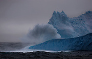 Wave breaking over Iceberg in the Southern Ocean. That's a couple of petrels you can see flying by the lower part of the berg, gives a sense of scale. ..