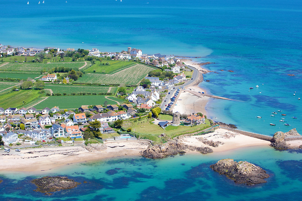Aerial view of the turquoise, clear, calm water at La Rocque beach in summer in Jersey, Channel islands