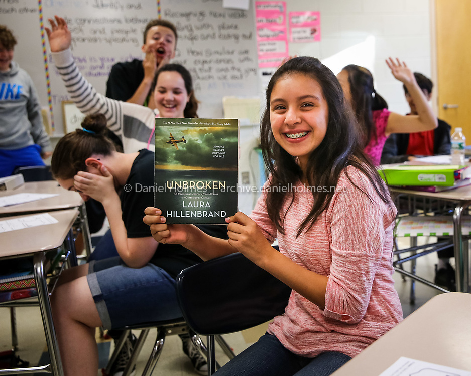 (9/24/14, FRANKLIN, MA) On Wednesday morning at Horace Mann School, 8th-grader, Christinna Fuentes, shows the young adult edition of the book, Unbroken, by Laura Hillenbrand, that students at the school will be reading this Fall. This is the fourth year that the 'All In' school-wide reading initiative as been offered at the Horace Mann School in Franklin. Daily News and Wicked Local Photo/Dan Holmes