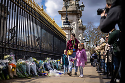 © Licensed to London News Pictures. 09/04/2021. London, UK. Josiah, 4 (L) and Nevaeh, 7 (R) lay flowers outside Buckingham Palace with their mother Tasha Pettman, following news of the death of Prince Philip. The Duke of Edinburgh Prince Philip, Queen Elizabeth II's husband, has died aged 99 Buckingham Palace has announced. Photo credit: Rob Pinney/LNP