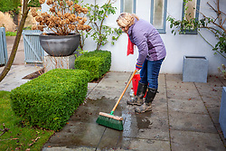Cleaning a patio using a long-handled brush, water and vinegar