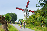 Adult cyclists riding bicycles past traditional Schellemolen windmill at Damme, West Flanders in Belgium